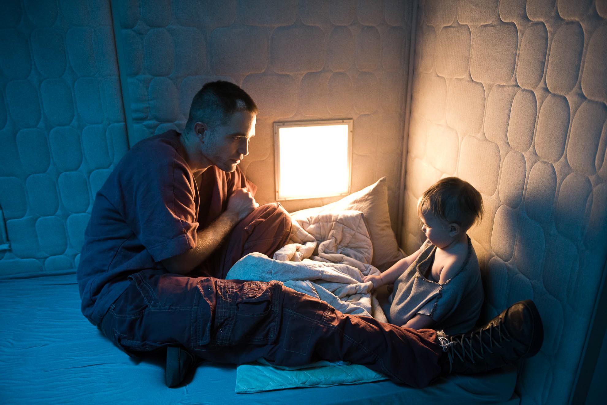 Robert PAttinson en el papel de Monte junto con el bebé de pocos meses que interpreta a Willow, su hija. Ambos descansan en la cama de un decorado futurista en un fotogframa de la película High Life de Claire Denis.