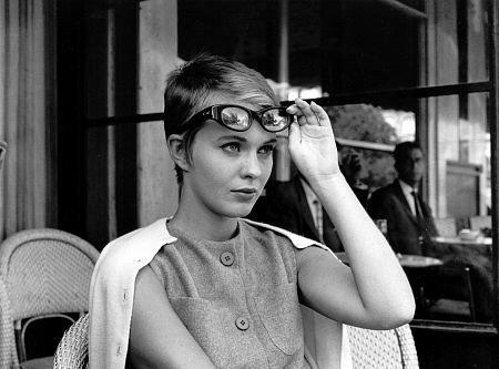 Jean Seberg, una de las actrices de la nouvelle vague, sujetando unas gafas vintage con su mano sobre su frente, sentada en la terraza de un café