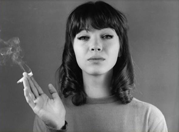 Anna KArina, una de las actrices ed la Nouvelle Vague, mirando a cámada y sosteniendo un cigarrillo humeando en su mano