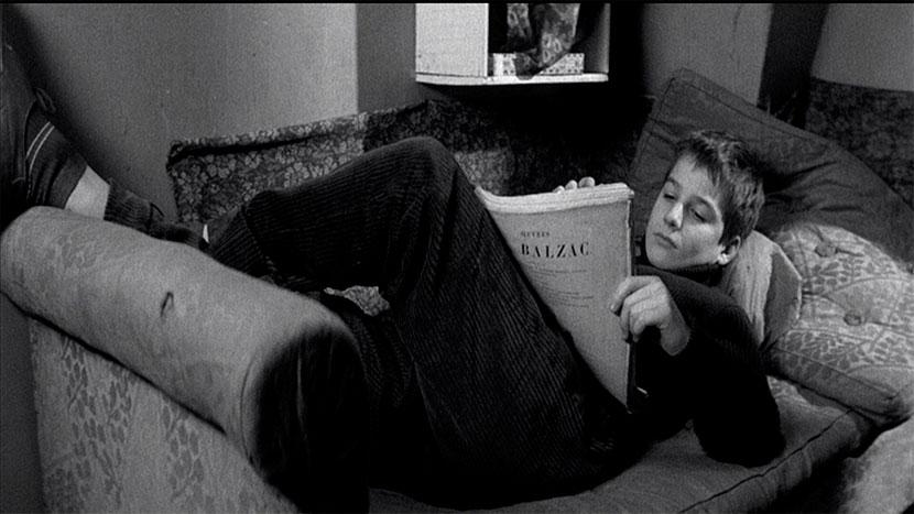 El joven Antoine Doinel lee a Balzac tumbado en un sofá