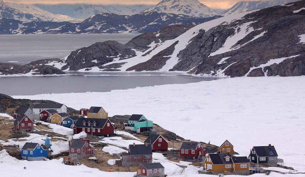 Paisaje nevado con montaña al fondo que muestra una pequeña aldea compuesta por casas de colores donde se rodó la película Un profesor en Groenlandia, del director de cine francés Samuel Collardey.