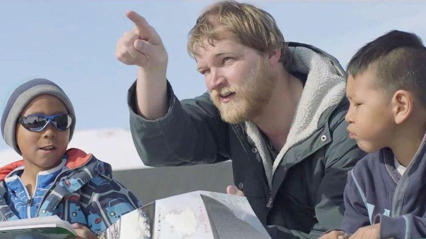 Anders, el protagonista de Un profesor en Groenlandia explica algo a dos niños mientras señala con el dedo y sotiene unos papeles. El sol inunca toda la escena en lque aparece un fondo de nieve con cielo azul
