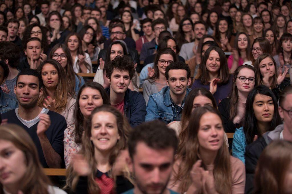Los dos protagonistas de Mentes brillantes sentados en un aula mirando al frente rodeados de otros estudiantes
