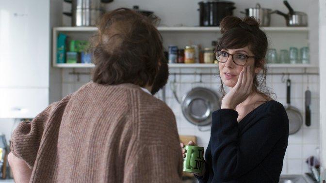 Dos personajes de la película Dobles vidas dialogan de pie, enfrentados, en una cocina,