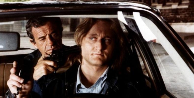 Fotograma de la película del éxito del cine polar en el 81 El profesional. Vemos a Belmondo sentado en la parte trasera de un coche apuntando con un arma al conductor.