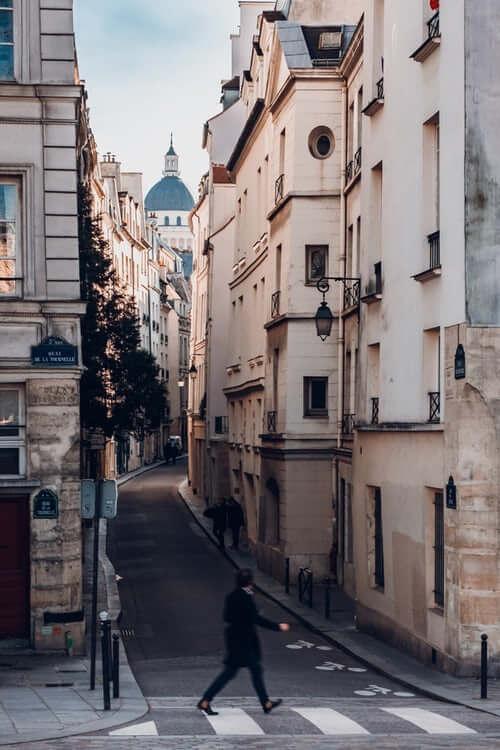 Hombre cruzando una calle estrecha y observando la ciudad