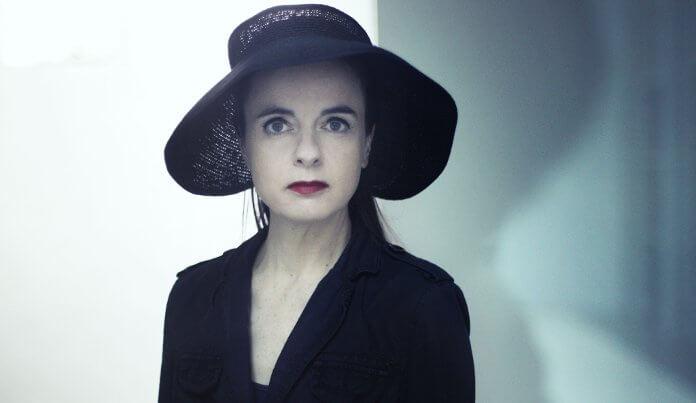 La autora más prolífica de la literatura francófona, AMélie Nothomb. Posando con un sombrero y vestida de negro, mirando a cámara.,
