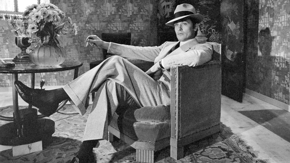 Alain Delon sentado en un sillón con traje y sombrero, icono del cine polar francés