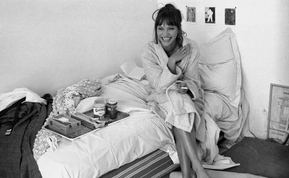 Anna Karina sentada en una cama en albornoz riendo y fumando un cigarrillo