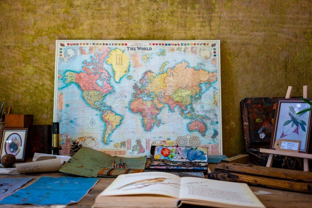 La traducción. Una mesa con mapa estilo vintage y algunos libros abiertos sobre ella delante de una pared en tonos ocres